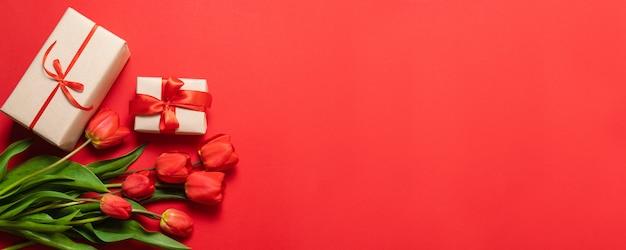 赤いチューリップと赤い背景の赤いリボンとギフトボックスの束。 Premium写真