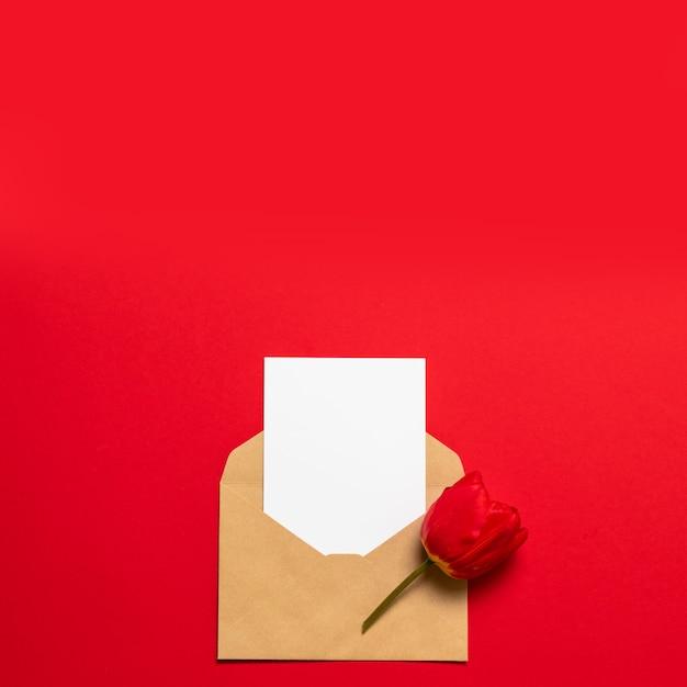 こんにちは春。赤いチューリップ、クラフト封筒、花と空白の白いはがきはがきチラシ Premium写真