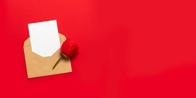 テキストと赤い背景の赤いチューリップのためのスペースと封筒 Premium写真
