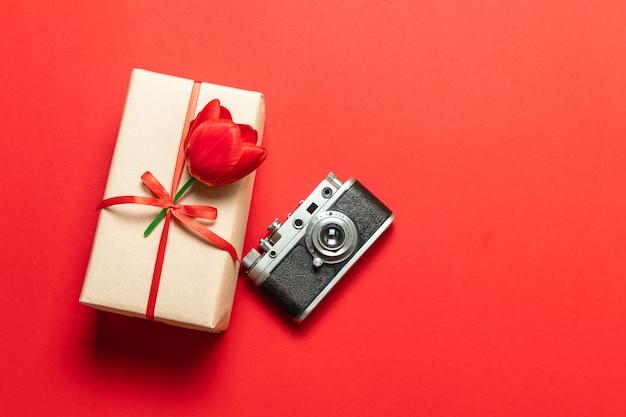 赤いリボンと赤い背景、古いモデルの写真カメラのチューリップとサプライズギフトボックス Premium写真