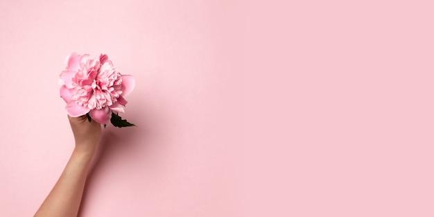 ピンクの小枝牡丹の花を持つ女性の手 Premium写真