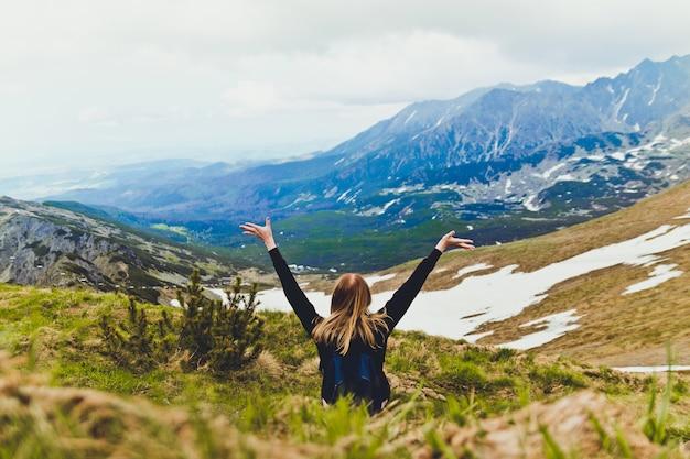 幸せな若いブロンド、青いバックパックと一緒に移動し、山の上に座っていると緑の山の風景を楽しんでいます Premium写真