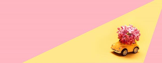 Желтый игрушечный автомобиль доставляет букет сирени на розовом желтом Premium Фотографии