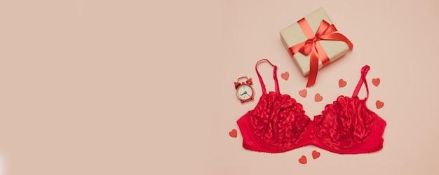 Красное женское нижнее белье с праздничной коробочкой с красным бантом на ленте Premium Фотографии