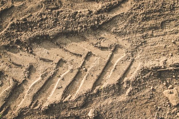 トラクターの車のタイヤのタイヤ踏面の痕跡と砂の道の茶色の土のテクスチャ。 Premium写真