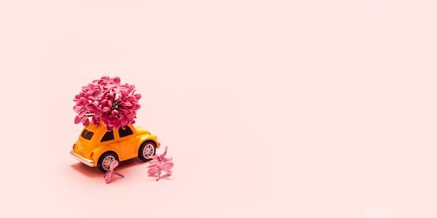Доставка свежих цветов к празднику. игрушка желтый автомобиль с сиреневый цветок филиал. Premium Фотографии