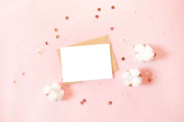 Открытка с бумажным конвертом, декором с блестками и хлопковыми цветами на розовом фоне Premium Фотографии