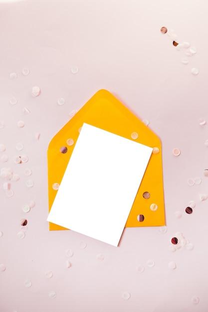 Творческая композиция с бумажным бланком и желтым конвертом на черном столе над головой для свадебной планировки Premium Фотографии