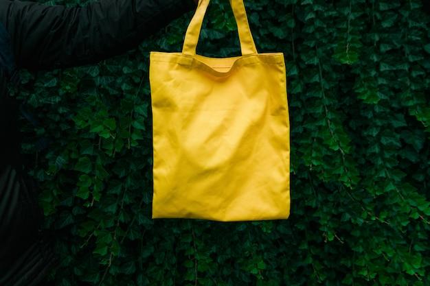 緑の植物の背景に手作りの買い物袋。空白のキャンバスバッグ、手でデザインのモックアップ。 Premium写真