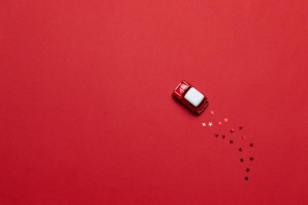 Маленький глянцевый игрушечный автомобиль с золотой звездой сверкает на красном фоне. праздничная открытка или баннер. Premium Фотографии