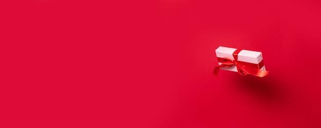 ピンクの紙と赤いサテンのリボンに包まれた美しいサプライズボックス Premium写真