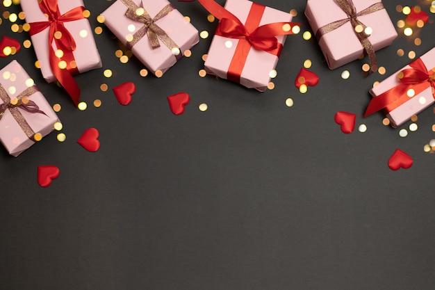 バレンタインデーの背景にサプライズギフト、ゴールドリボン、暗い背景に赤い愛の形 Premium写真