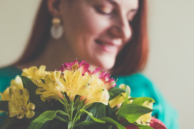 Красивая молодая женщина в зеленом платье держит букет весенних цветов Premium Фотографии