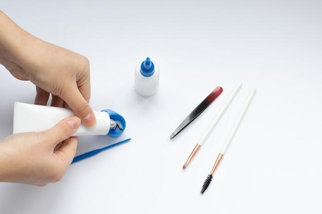 眉毛の染色と矯正のための道具一式、マスターの手 Premium写真