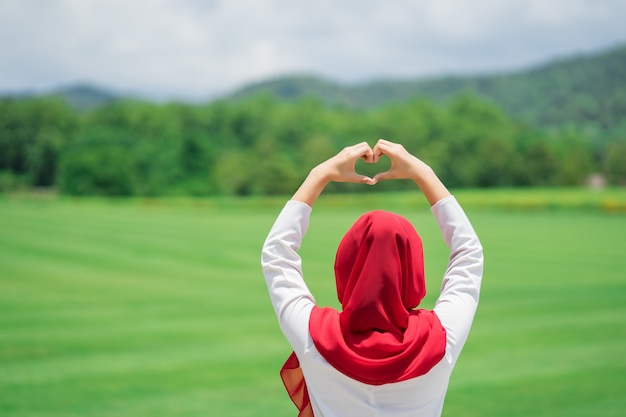 緑の野原で幸せな若いイスラム教徒の赤いヒジャーブの肖像画 Premium写真