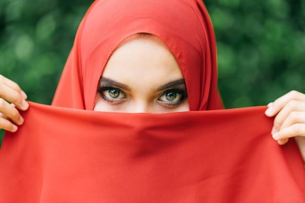 幸せな若いイスラム教徒の女性リフト手の美しい赤いヒジャーブで顔から布を取る Premium写真