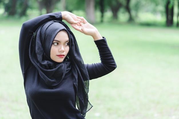 Красивая молодая мусульманская азиатская женщина делая тренировку перед бежать запачкала зеленое поле Premium Фотографии