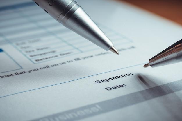 銀ペンのクローズアップは、契約方針契約書に署名しています。法的契約に署名します。 Premium写真