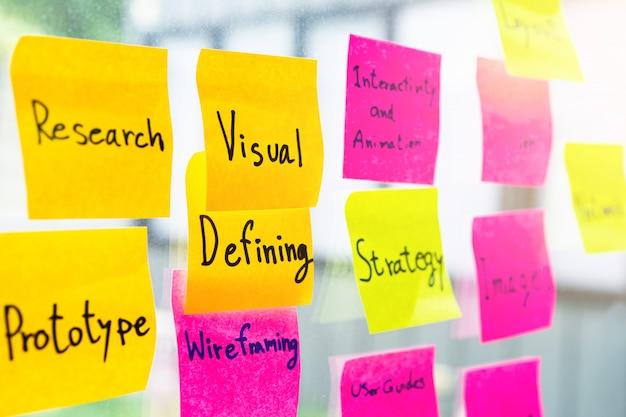 Красочное липкое примечание на стеклянной стене офиса с графическим дизайном связанным словом Premium Фотографии
