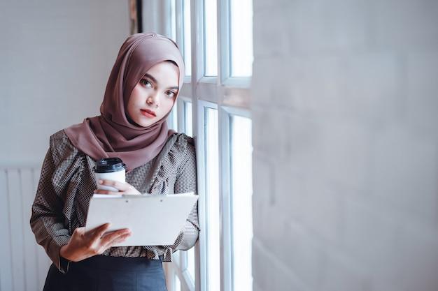 Арабская рука бизнес-леди держа деловые документы и бумажную кофейную чашку на рабочем месте офиса. Premium Фотографии