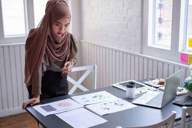 プロのアラブ女性実業家茶色ヒジャーブ立って、金融投資プロジェクトグラフチャートレポートをチェックインします。 Premium写真