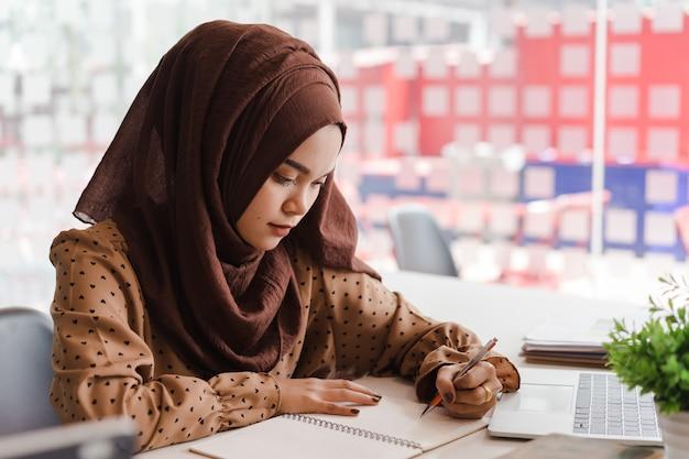 スマートカジュアルな服装、ビジネス、創造的なコワーキングに座って笑顔で若いアジアのイスラム教徒のビジネス女性。 Premium写真