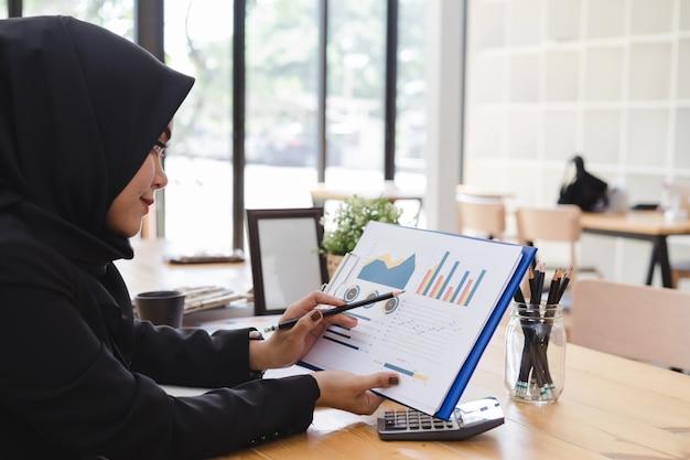 コワーキングやコーヒーショップで若いイスラム教徒のビジネス女性黒ヒジャーブビジネスレポート。 Premium写真
