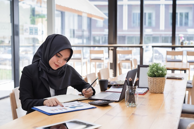 コワーキングで働く黒ヒジャーブを着ている若いイスラム教徒のビジネス人々の肖像画。 Premium写真