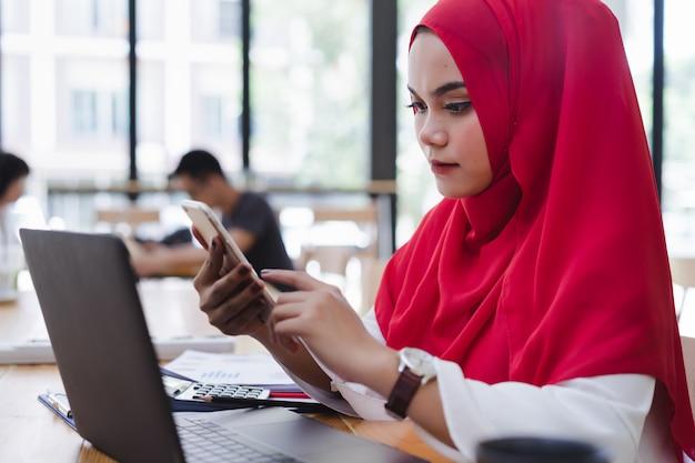 Хиджаб привлекательного азиатского мусульманского бухгалтера красный используя телефон и финансовые отчеты в со-работе. Premium Фотографии