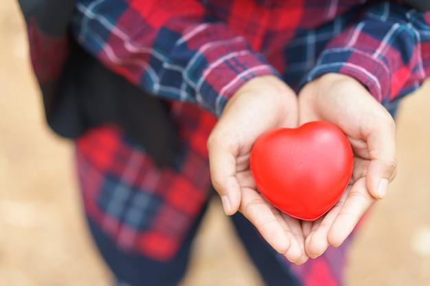 赤いハート、健康、薬、慈善を与える女性の手。 Premium写真