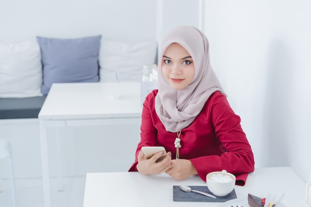 彼女の携帯電話を使用して幸せな若いイスラム教徒の女性の肖像画。 Premium写真