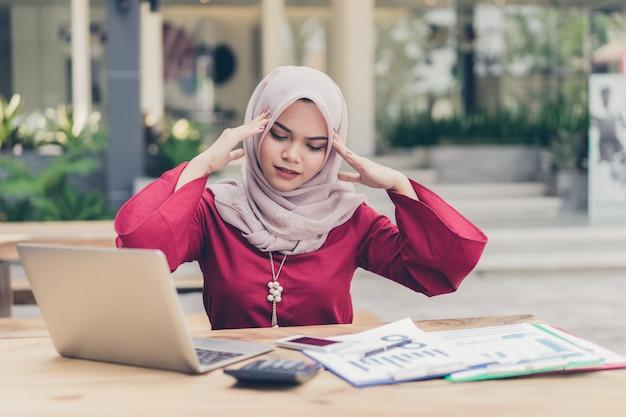 Серьезно азиатских мусульманских бизнес женщина имеет головную боль. Premium Фотографии