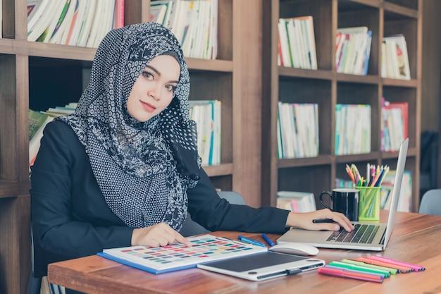 Счастливая молодая мусульманская творческая дизайнерская женщина используя образцы цветовой палитры и компьтер-книжку перед книжными полками. Premium Фотографии