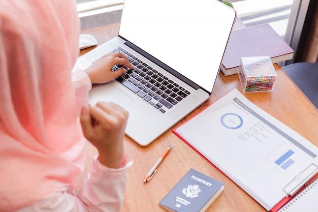 Привлекательная мусульманская деловая женщина сша достигает целей. пустой экран ноутбука Premium Фотографии