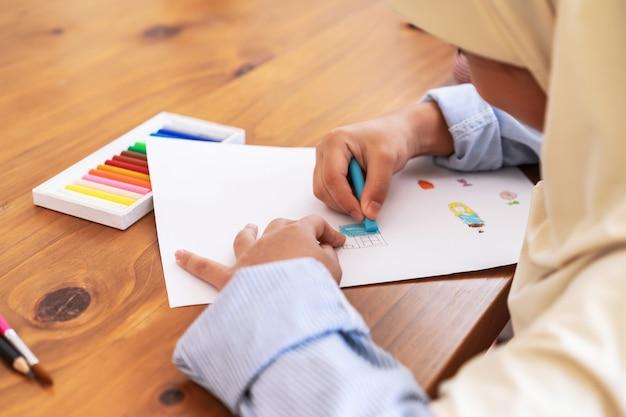 Милая маленькая мусульманская девушка наслаждаясь красить в школе. концепция образования, школы, искусства и живописи Premium Фотографии