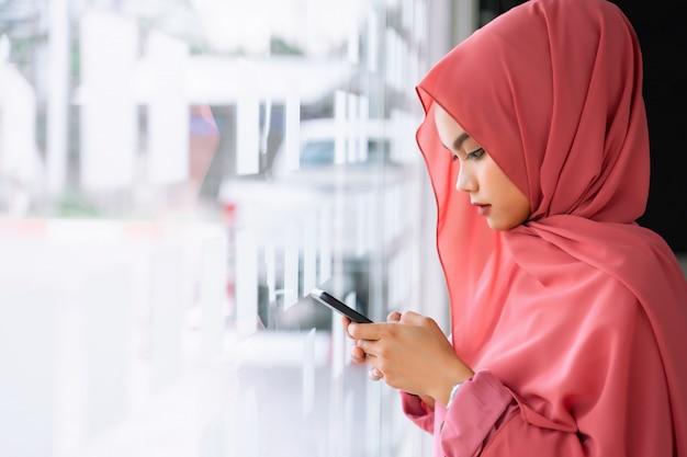 職場でスマートな携帯電話を使用して美しい若いイスラム教徒のビジネス女性。共同作業スペースで若いイスラム教徒のピンクのヒジャーブの肖像画。 Premium写真