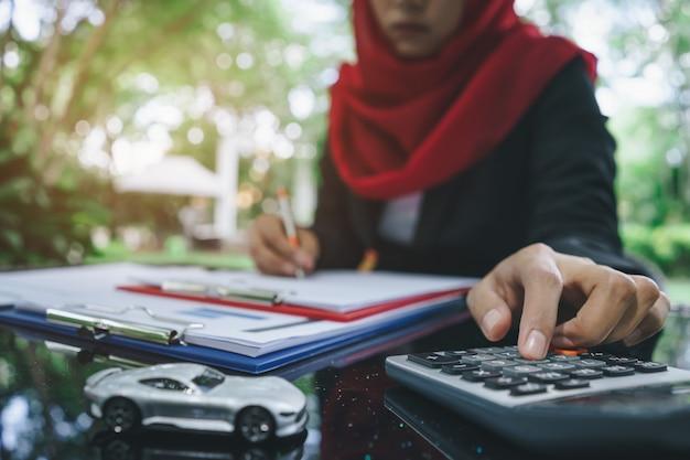 ビジネスのイスラム教徒の女性の手が自動車保険の見積もりを書き、計算する Premium写真