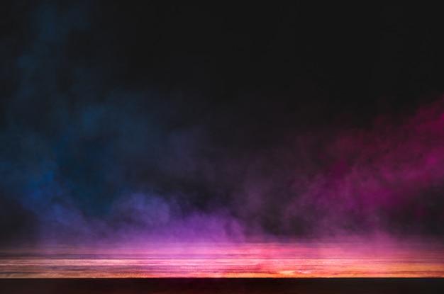 暗い背景にカラフルな煙が浮かぶ空の木製テーブル Premium写真