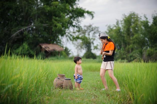 緑の田んぼで遊んでいる母とかわいい赤ちゃん、家族愛のコンセプト。 Premium写真