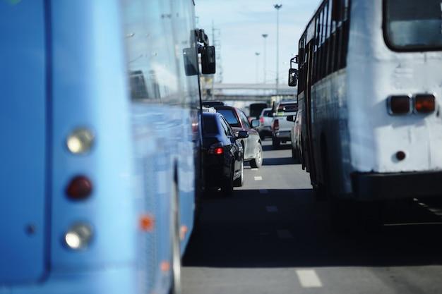 バス間のラッシュアワービューで混雑した交通道路でミニトラックの車線を変更 Premium写真