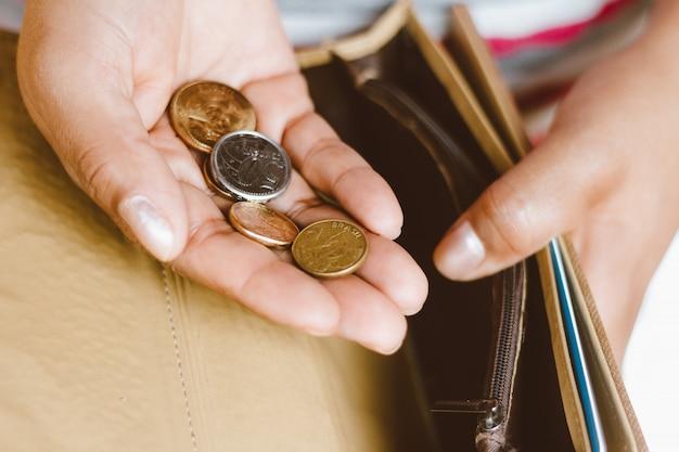 Женщина держа пустой бумажник с некоторыми монетками в ее руке - концепция экономического кризиса - деньги сбережений для финансового учета. Premium Фотографии