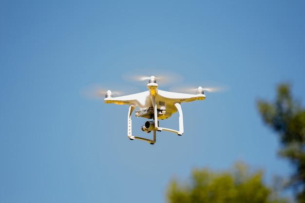 Дрон летит в солнечный день Premium Фотографии