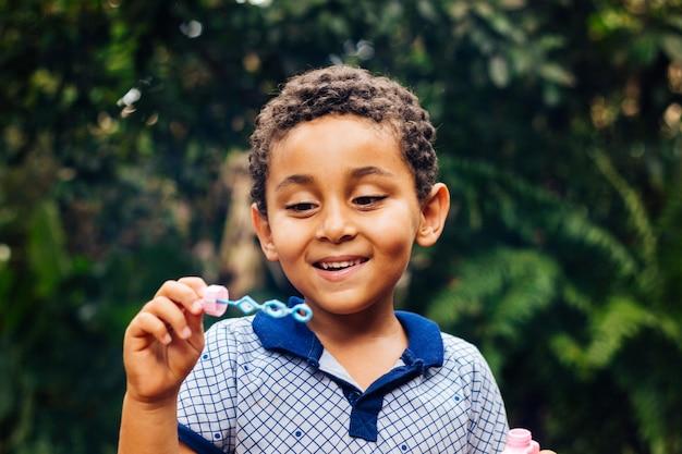 Улыбающийся мальчик играет мыльный пузырь Premium Фотографии