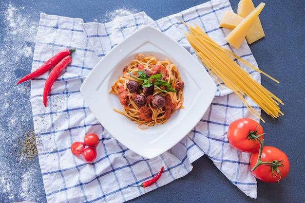 白いプレートにパスタボロネーゼ。青色の背景にスパゲッティ Premium写真