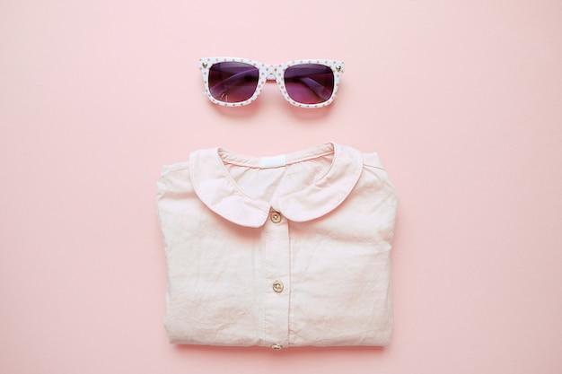 ピンクの背景に夏子供服のセットです。女の赤ちゃんのファッションに見えるシャツとメガネ Premium写真