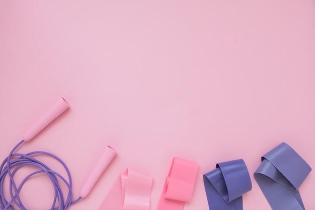 Прыжок или скакалка и фитнес-резинка на розовом фоне. фитнес-тренд. Premium Фотографии