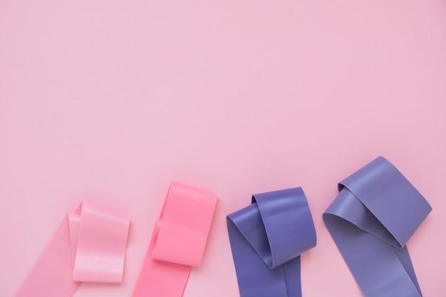 Фитнес-резинка, эластичные удлинители разных цветов для спорта, на розовом фоне. фитнес-тренд. Premium Фотографии