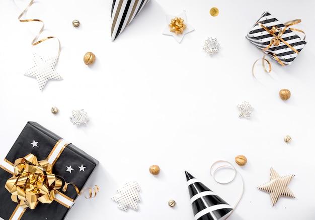 クリスマスの組成物。クリスマスプレゼント、パーティーハット、白い背景に黒と金の装飾。平干し、コピースペース Premium写真