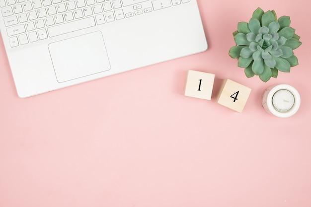 フラットレイアウトのホームオフィスデスク。ピンクの表面にラップトップと装飾が施された女性ワークスペース。バレンタインデーのコンセプト Premium写真