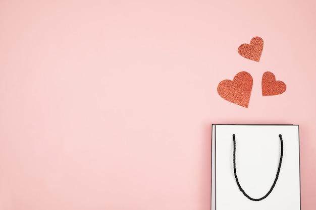 Баннер, флаер или плакат макет для продажи день матери, белая сумка на розовой поверхности. бумажный пакет для покупок с красными сердцами. день святого валентина, Premium Фотографии